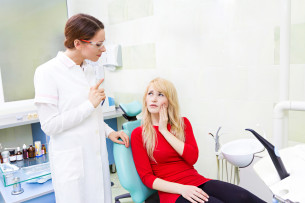woman with toothache and dentist explaining to her Dental Care Center